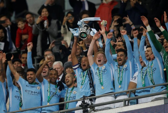 "Soccer Football - Carabao Cup Final - Arsenal vs Manchester City - Wembley Stadium, London, Britain - February 25, 2018   Manchester City's Vincent Kompany lifts the trophy as they celebrate winning the Carabao Cup   Action Images via Reuters/Carl Recine     EDITORIAL USE ONLY. No use with unauthorized audio, video, data, fixture lists, club/league logos or ""live"" services. Online in-match use limited to 75 images, no video emulation. No use in betting, games or single club/league/player publications. Please contact your account representative for further details."