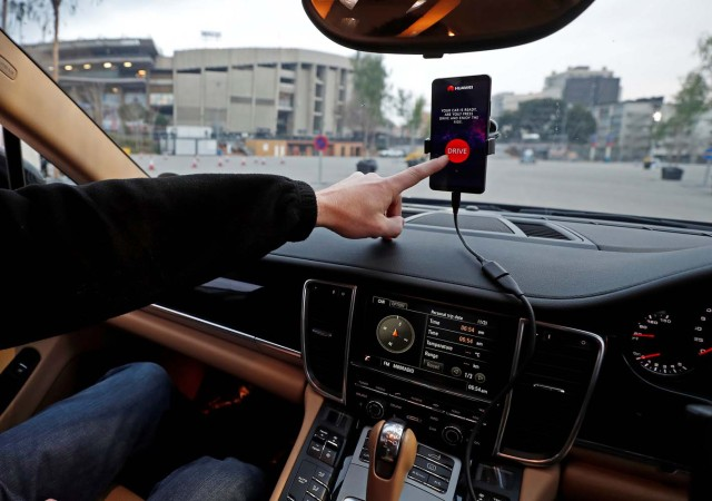 An engineer points to a Huawei Mate 10 Pro mobile used to control a driverless car during the Mobile World Congress in Barcelona, Spain February 26, 2018. REUTERS/Yves Herman