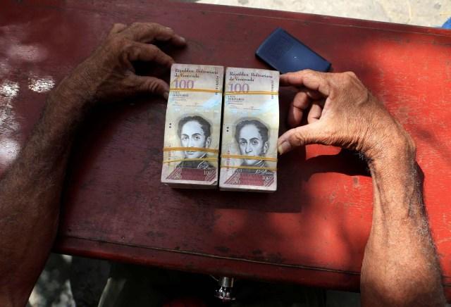 Un cambiador de dinero se sienta en una mesa en la frontera entre Colombia y Venezuela, en Paraguachon, Colombia 16 de febrero de 2018. Fotografía tomada el 16 de febrero de 2018. REUTERS / Jaime Saldarriaga