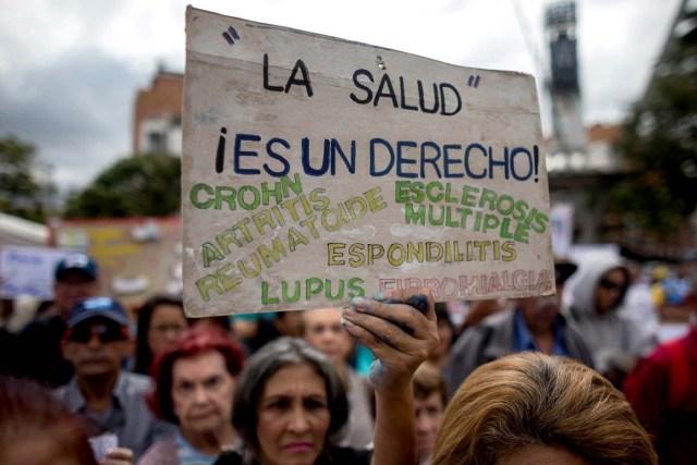 ACOMPAÑA CRÓNICA: VENEZUELA CRISIS ** CAR021. CARACAS (VENEZUELA), 08/02/2018.- Una mujer muestra un cartel durante una protesta por la escasez de medicinas y tratamientos para la salud hoy, jueves 8 de febrero de 2018, en Caracas (Venezuela). Una plaza del este de Caracas sirvió hoy de escenario para que decenas de enfermos venezolanos expresaran su frustración por la imposibilidad de acceder a los tratamientos médicos que necesitan para seguir con vida y también para informar acerca de la grave crisis sanitaria por la que pasa Venezuela. EFE/MIGUEL GUTIÉRREZ