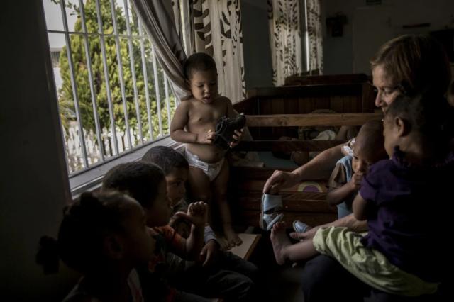 Un cuidador ayuda a un niño a vestirse en Bambi House, un orfanato privado en Caracas, Venezuela. (Alejandro Cegarra for The Washington Post)
