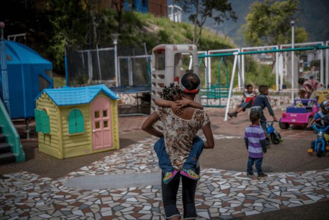 Dayana Silgado lleva a su hija al patio de recreo minutos antes del final de una visita a Fundana. Silgado no puede proporcionar suficiente comida para sus hijos, por lo que colocó a dos de ellos en el centro. (Alejandro Cegarra for The Washington Post