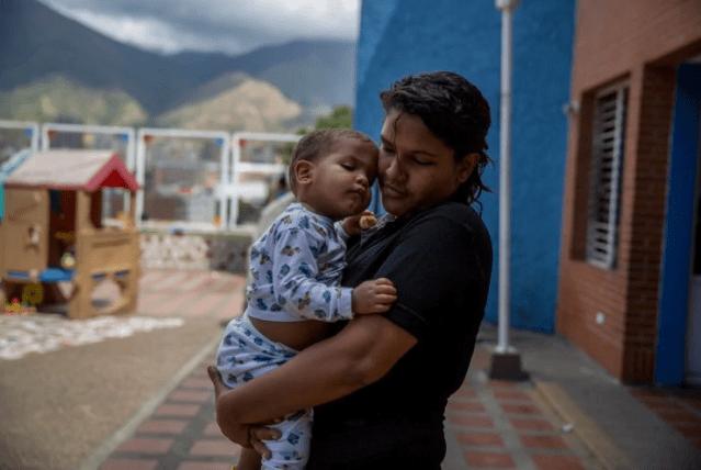 En una visita a Fundana un domingo, Melani Morales abraza a su hijo Christopher, a quien ella colocó allí porque no puede permitirse cuidarlo. (Alejandro Cegarra for The Washington Post)