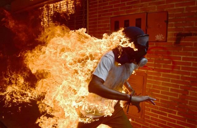 En esta foto de archivo tomada el 3 de mayo de 2017 Un manifestante se incendia durante los enfrentamientos con la policía antidisturbios en una protesta contra el presidente venezolano, Nicolás Maduro. Una imagen abrasadora de un manifestante venezolano que se incendió durante los enfrentamientos con la policía antidisturbios ha ganado al fotógrafo de AFP Ronaldo Schemidt una nominación para el premio World Press Photo 2018. El pargo con sede en México de Agence France-Presse se encuentra entre los seis fotógrafos, elegidos entre más de 4.500 aspirantes, para ser nominados para el prestigioso premio anual, la World Press Photo Foundation en Amsterdam reveló el 14 de febrero de 2018. / AFP PHOTO / RONALDO SCHEMIDT