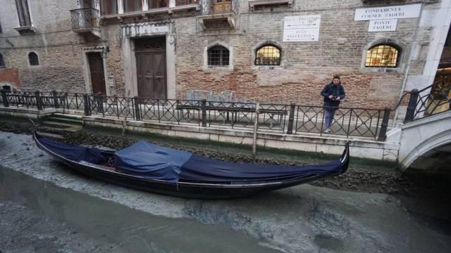 Una góndola permanece amarrada en un canal prácticamente sin agua en Venecia. (Efe)