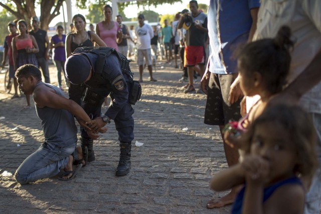 A man is detained inside the improvised Venezuelan refugee camp at Simon Bolivar square, accused of trying to molest a child, in the city of Boa Vista, Roraima, Brazil, on February 25, 2018. According to local authorities, around one thousand refugees are crossing the Brazilian border each day from Venezuela. With the constant influx of Venezuelan immigrants, most are living in shelters and the streets of Boa Vista and Pacaraima cities, looking for work, medical care and food. Most are legalizing their status to stay and live in Brazil. / AFP PHOTO / Mauro PIMENTEL
