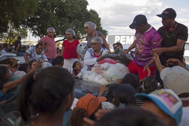 Los refugiados venezolanos se reúnen para recibir ropa distribuida por voluntarios en la plaza Simón Bolívar en la ciudad de Boa Vista, Roraima, Brasil, el 25 de febrero de 2018. Cuando el flujo migratorio venezolano estalló en 2017, la ciudad de Boa Vista, capital del estado de Roraima, a 200 kilómetros de la frontera con Venezuela, comenzó a establecer refugios a medida que la gente comenzaba a establecerse en plazas, parques y rincones de esta ciudad de 330,000 habitantes habitantes de los cuales el 10 por ciento es ahora venezolano. / AFP PHOTO / Mauro PIMENTEL
