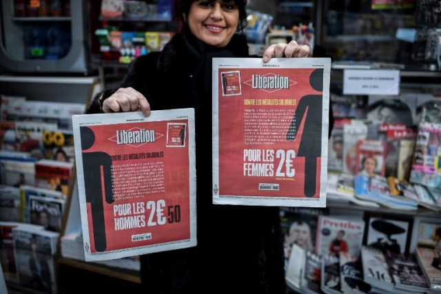 A woman holds the two different front pages of the French daily newspaper Liberation during the International Woman's Day on March 8, 2018 in Paris. / AFP PHOTO / STEPHANE DE SAKUTIN