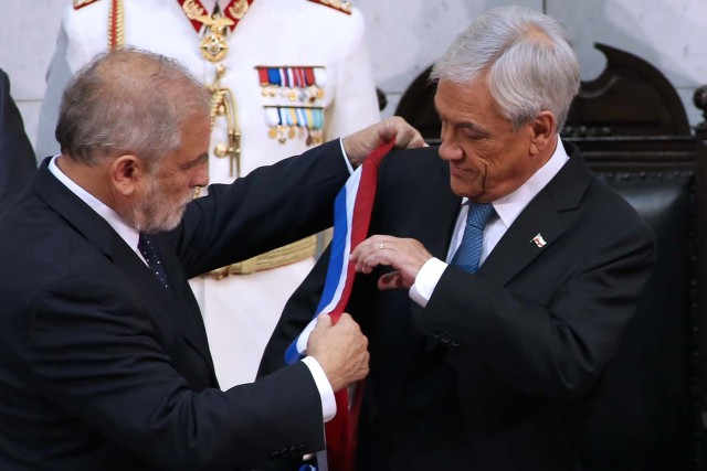 Chile's new President Sebastian Pinera (R) receives the presidential sash from Senate President Carlos Montes during his inauguration ceremony at the Congress in Valparaiso, Chile, on March 11, 2018. Rightwing billionaire businessman Pinera was sworn in as the new president of Chile for the second time. / AFP PHOTO / CLAUDIO REYES