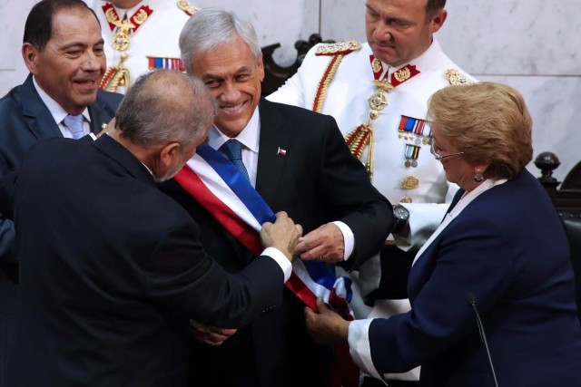 Chile's new President Sebastian Pinera (C) receives the presidential sash from Senate President Carlos Montes (L) while outgoing President Michelle Bachelet (R) helps them during the inauguration ceremony at the Congress in Valparaiso, Chile, on March 11, 2018. Rightwing billionaire businessman Pinera was sworn in as the new president of Chile for the second time. / AFP PHOTO / CLAUDIO REYES
