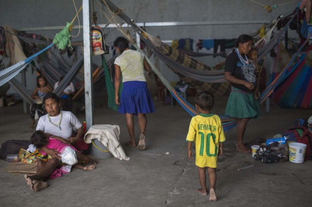 Venezuelan indigenous refugees rest inside a temporary shelter in the city of Pacaraima, Roraima, Brazil, on February 28, 2018. Hundreds of Venezuelan indigenous people, most of them Warao indigenous, from the northeast of the country, escaped from turmoil and hunger to Brazil during last years. In improvised shelters the situation has improved for some of them, but the migration increasing influx and the lack of plans generates uncertainty. / AFP PHOTO / Mauro Pimentel / TO GO WITH AFP STORY by Paula RAMÓN
