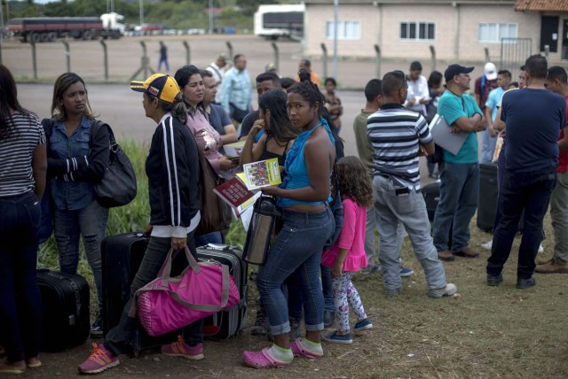 Venezuelans wait in a queue in front of the Brazil Federal Police Office in the Venezuela-Brazil border, at Pacaraima, Roraima, Brazil, on February 28, 2018. According to local authorities, around one thousand refugees are crossing the Brazilian border each day from Venezuela. With the constant influx of Venezuelan immigrants, most are living in shelters and the streets of Boa Vista and Pacaraima cities, looking for work, medical care and food. Most are legalizing their status to stay and live in Brazil. / AFP PHOTO / Mauro Pimentel / TO GO WITH AFP STORY by Paula RAMÓN