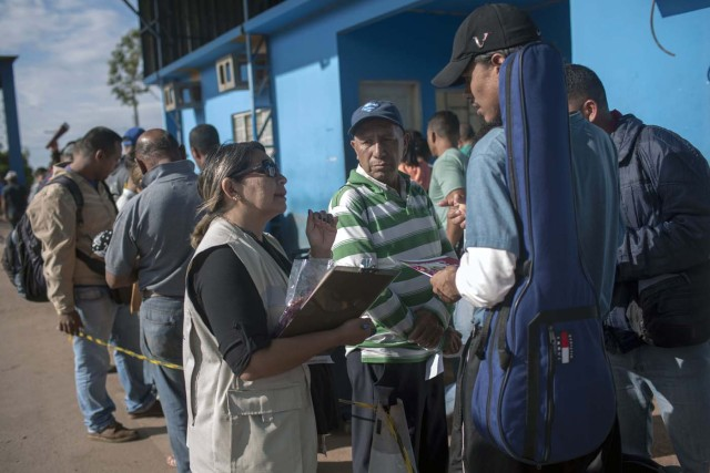 A Brazilian Health Surveillance worker talks with Venezuelans waiting in queue in front of the Brazil Federal Police Office in the border between Venezuela and Brazil at Pacaraima, Roraima, Brazil, on February 28, 2018. According to local authorities, around one thousand refugees are crossing the Brazilian border each day from Venezuela. With the constant influx of Venezuelan immigrants, most are living in shelters and the streets of Boa Vista and Pacaraima cities, looking for work, medical care and food. Most are legalizing their status to stay and live in Brazil. / AFP PHOTO / Mauro Pimentel / TO GO WITH AFP STORY by Paula RAMÓN