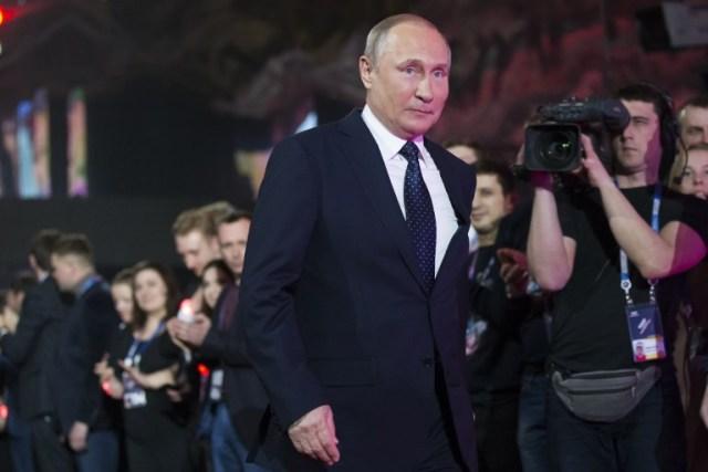 """El presidente ruso, Vladimir Putin, llega para pronunciar un discurso en un foro de jóvenes """"Rusia, tierra de oportunidades"""" en Moscú el 15 de marzo de 2018. Rusia votará por presidente el 18 de marzo de 2018. / AFP PHOTO / POOL / Alexander Zemlianichenko"""