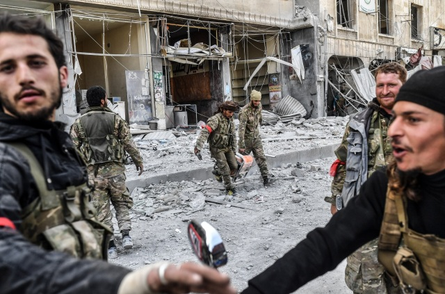 sirios respaldados por Turquía se reúnen en la ciudad de Afrin, en el norte de Siria, el 18 de marzo de 2018. Las fuerzas turcas y sus aliados rebeldes controlaban la ciudad de Afrin, de mayoría kurda, en el noroeste de Siria, informaron periodistas de la AFP. / AFP PHOTO / Bulent Kilic