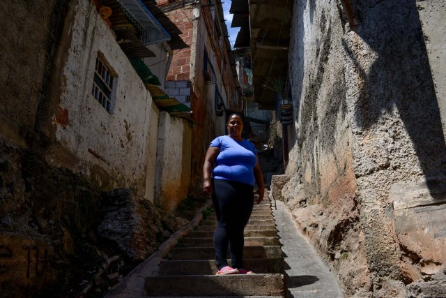 (FILES) In this file photo taken on February 28, 2018 Gabriela Vega, 35, community leader and cook poses for a picture at La Vega shantytown in Caracas. / AFP PHOTO / FEDERICO PARRA