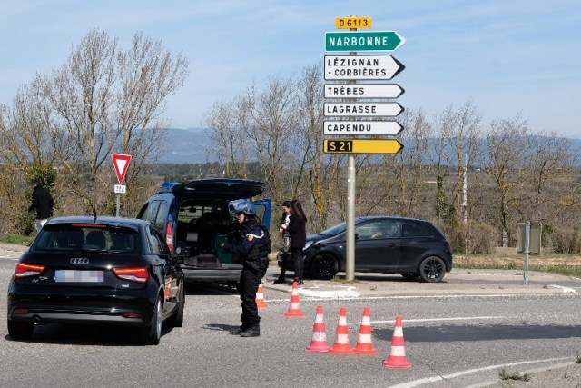 French gendarmes block the access to Trebes, where a man took hostages at a supermarket on March 23, 2018 in Trebes, southwest France.   At least one person was feared dead after a gunman claiming allegiance to the Islamic State group fired shots in a hostage-taking at a supermarket in southwest France, police said. / AFP PHOTO / ERIC CABANIS