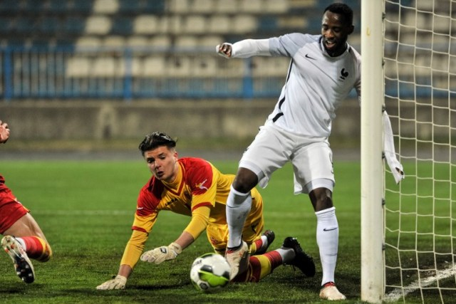 France's Moussa Dembele (R) vies with Montenegrin goalkeeper Matija Sarkic (L) during the Euro 2018 U-21 qualifying football match between Montenegro and France at Gradski Stadium in Niksic on March 27, 2018.  / AFP PHOTO / SAVO PRELEVIC