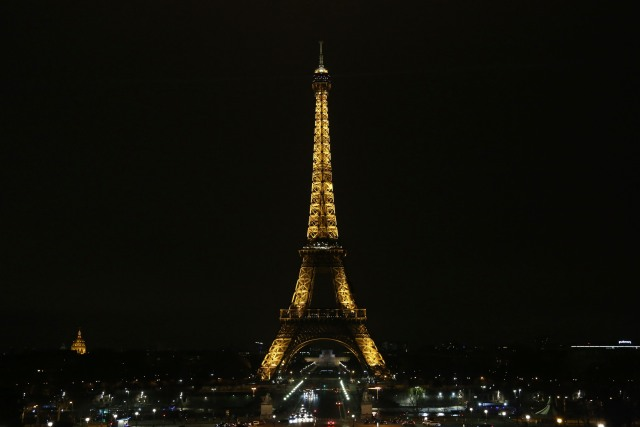 The lights of the Eiffel Tower are seen before they are dimmed at midnight, March 23, 2018 in Paris to honor victims killed at a supermarket in southwest France by a man claiming allegiance to the Islamic State. Paris Mayor Anne Hidalgo announced that the Eiffel Tower would switch off its light at midnight to honour the victims. / AFP PHOTO / Zakaria ABDELKAFI