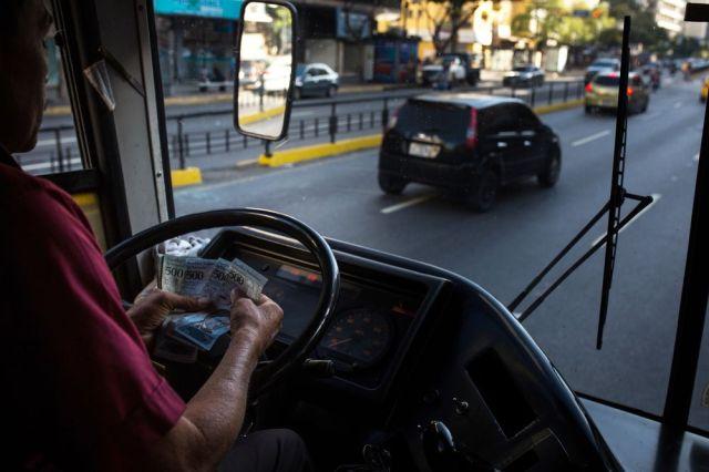 Un conductor de autobús cuenta los bolívares en Caracas. Fotógrafo: Wil Riera / Bloomberg