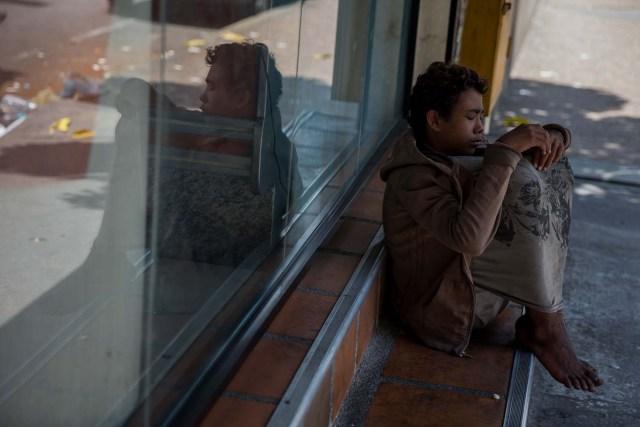 Fotografía del 3 de marzo de 2018 de un adolescente en la entrada de una panadería en Caracas (Venezuela). La inédita crisis económica y social de Venezuela se hace inocultable en calles y casas de abrigo que a diario reciben a niños que han quedado desamparados después de que sus padres emigraran a otro país a buscar nuevas formas de ingresos y los dejaran a cargo de personas que no pueden mantenerlos. EFE/MIGUEL GUTIÉRREZ
