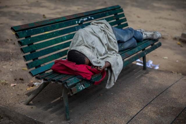 Fotografía del 3 de marzo de 2018 de un adolescente durmiendo en una silla en una plaza en Caracas (Venezuela). La inédita crisis económica y social de Venezuela se hace inocultable en calles y casas de abrigo que a diario reciben a niños que han quedado desamparados después de que sus padres emigraran a otro país a buscar nuevas formas de ingresos y los dejaran a cargo de personas que no pueden mantenerlos. EFE/MIGUEL GUTIÉRREZ
