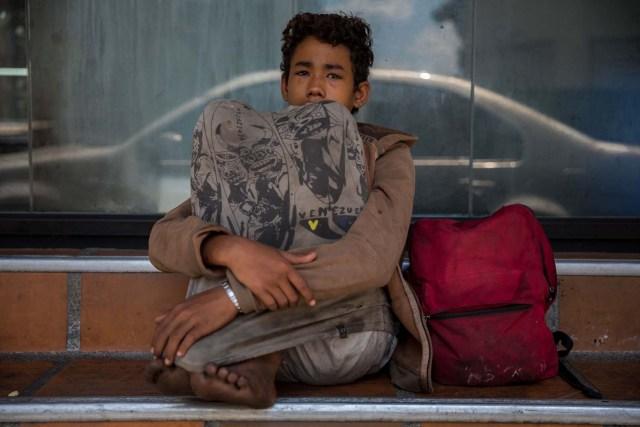 Fotografía del 3 de marzo de 2018 de un adolescente en la entrada de una panadería en una plaza en Caracas (Venezuela). La inédita crisis económica y social de Venezuela se hace inocultable en calles y casas de abrigo que a diario reciben a niños que han quedado desamparados después de que sus padres emigraran a otro país a buscar nuevas formas de ingresos y los dejaran a cargo de personas que no pueden mantenerlos. EFE/MIGUEL GUTIÉRREZ