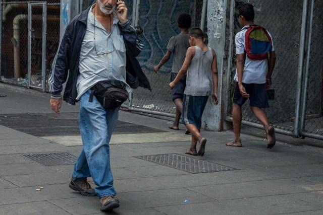 Fotografía del 3 de marzo de 2018 de niños caminando en un calle de Caracas (Venezuela). La inédita crisis económica y social de Venezuela se hace inocultable en calles y casas de abrigo que a diario reciben a niños que han quedado desamparados después de que sus padres emigraran a otro país a buscar nuevas formas de ingresos y los dejaran a cargo de personas que no pueden mantenerlos. EFE/MIGUEL GUTIÉRREZ