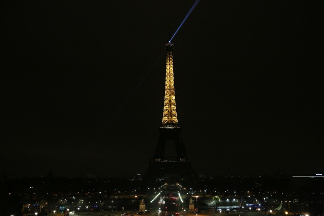 The lights of the Eiffel Tower are dimmed at midnight, March 23, 2018 in Paris to honor victims killed at a supermarket in southwest France by a man claiming allegiance to the Islamic State. Paris Mayor Anne Hidalgo announced that the Eiffel Tower would switch off its light at midnight to honour the victims. / AFP PHOTO / Zakaria ABDELKAFI