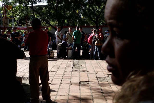 "People traveling by bus from Caracas to Ecuador wait in line to stamp their passports at the migration control office in San Antonio del Tachira, Venezuela, November 8, 2017. After more than twelve hours traveling, crossing into Colombia was for many on the bus the first time they had left Venezuela. When they arrived at the migration office, it was temporarily closed because the computers were down. Travelers had to wait in line about three hours to get their documents stamped. REUTERS/Carlos Garcia Rawlins  SEARCH ""RAWLINS BUS"" FOR THIS STORY. SEARCH ""WIDER IMAGE"" FOR ALL STORIES."