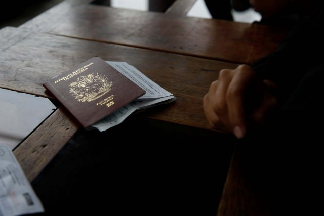 """Alejandra Rodriguez, who is traveling by bus from Caracas to Chile, puts her passport on a desk while she waits in line to stamp it at the binational border service centre in Huaquillas, Ecuador, November 11, 2017. REUTERS/Carlos Garcia Rawlins SEARCH """"RAWLINS BUS"""" FOR THIS STORY. SEARCH """"WIDER IMAGE"""" FOR ALL STORIES."""