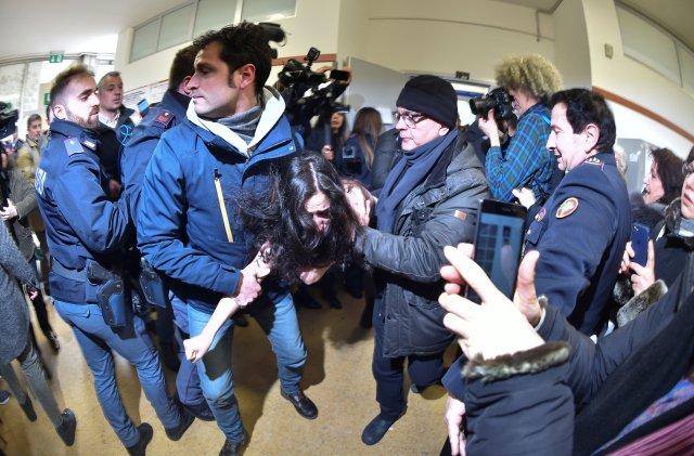 La policía italiana bloquea a un activista del grupo de derechos femeninos Femen en la mesa de votación donde el líder del partido Forza Italia, Silvio Berlusconi, emitió su voto en Milán, Italia, el 4 de marzo de 2018. Fotografía tomada con una lente ojo de pez. REUTERS / Alberto Lingria