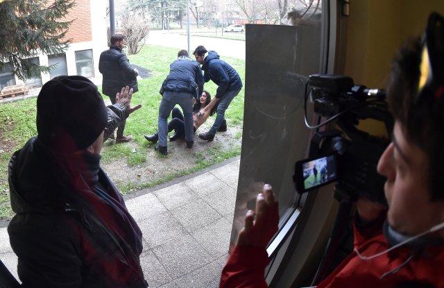 Policías italianos bloquean a un activista del grupo Femen de los derechos de las mujeres en la mesa de votación donde el líder del partido Forza Italia, Silvio Berlusconi, emitió su voto en Milán, Italia el 4 de marzo de 2018. Fotografía tomada con una lente ojo de pez. REUTERS / Alberto Lingria
