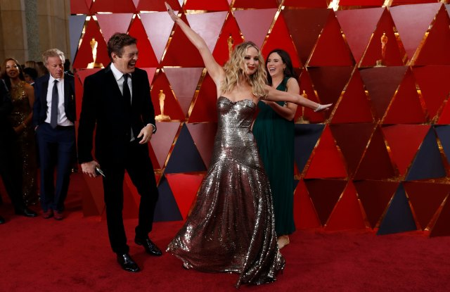 90th Academy Awards - Oscars Arrivals - Hollywood, California, U.S., 04/03/2018 - Jennifer Lawrence poses as Jason Blum (L) and Lauren Schuker (R) look on. REUTERS/Carlo Allegri