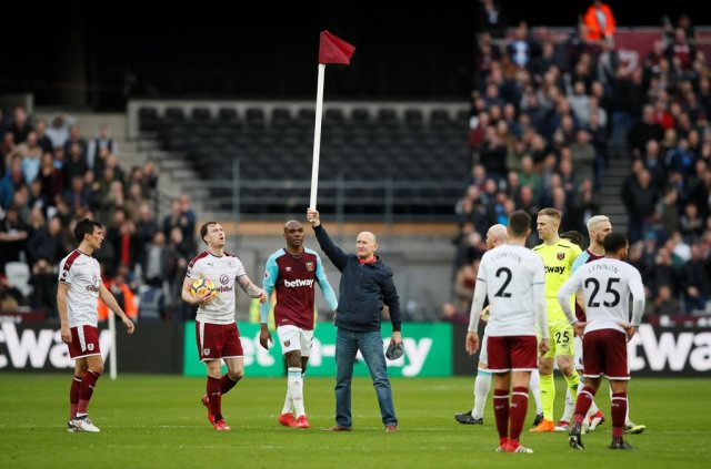 """Soccer Football - Premier League - West Ham United vs Burnley - London Stadium, London, Britain - March 10, 2018 Fan holds up a corner flag after invading the pitch REUTERS/David Klein EDITORIAL USE ONLY. No use with unauthorized audio, video, data, fixture lists, club/league logos or """"live"""" services. Online in-match use limited to 75 images, no video emulation. No use in betting, games or single club/league/player publications. Please contact your account representative for further details."""
