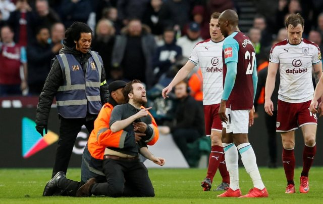 """Soccer Football - Premier League - West Ham United vs Burnley - London Stadium, London, Britain - March 10, 2018 Fan is tackled by stewards after invading the pitch REUTERS/David Klein EDITORIAL USE ONLY. No use with unauthorized audio, video, data, fixture lists, club/league logos or """"live"""" services. Online in-match use limited to 75 images, no video emulation. No use in betting, games or single club/league/player publications. Please contact your account representative for further details. TPX IMAGES OF THE DAY"""