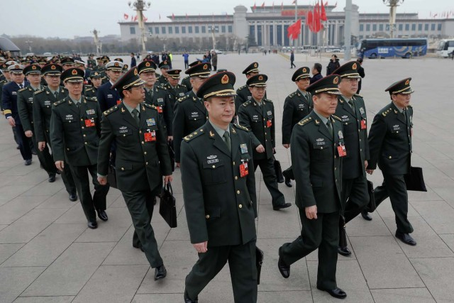 Military delegates arrive to the third plenary session of the National People's Congress (NPC) at the Great Hall of the People to take a part in a vote on a constitutional amendment lifting presidential term limits, in Beijing, China March 11, 2018. REUTERS/Damir Sagolj
