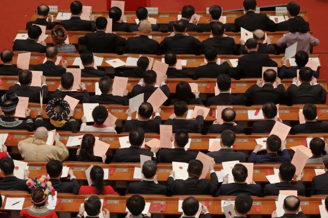 Delegates check ballots before a vote on a constitutional amendment lifting presidential term limits during the third plenary session of the National People's Congress (NPC) at the Great Hall of the People in Beijing, China March 11, 2018. REUTERS/Damir Sagolj