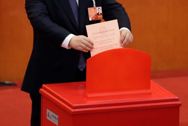 Chinese President Xi Jinping drops his ballot during a vote on a constitutional amendment lifting presidential term limits, at the third plenary session of the National People's Congress (NPC) at the Great Hall of the People in Beijing, China March 11, 2018. REUTERS/Jason Lee