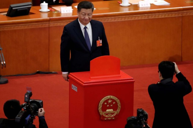 Chinese President Xi Jinping pauses after casting his ballot during a vote on a constitutional amendment lifting presidential term limits, at the third plenary session of the National People's Congress (NPC) at the Great Hall of the People in Beijing, China March 11, 2018. REUTERS/Jason Lee