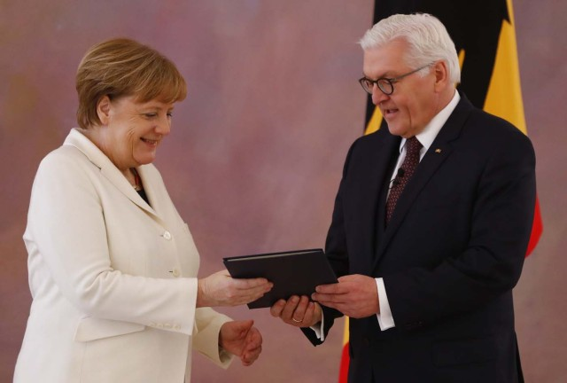 German Chancellor Angela Merkel receives her certificate of appointment from President Frank-Walter Steinmeier after being re-elected as chancellor, during a ceremony at Bellevue Palace in Berlin, Germany, March 14, 2018. REUTERS/Fabrizio Bensch