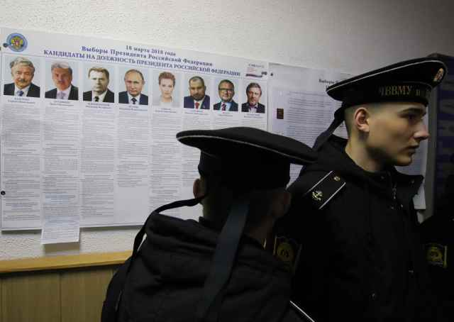Russian navy sailors gather near a broadsheet with information about the candidates at a polling station during the Russian presidential election in Sevastopol, Crimea March 18, 2018. REUTERS/Pavel Rebrov