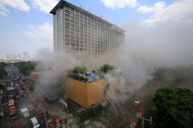 Los bomberos empapan agua después de que un incendio envolvió el hotel Manila Pavilion en Metro Manila, Filipinas el 18 de marzo de 2018. REUTERS / Romeo Ranoco