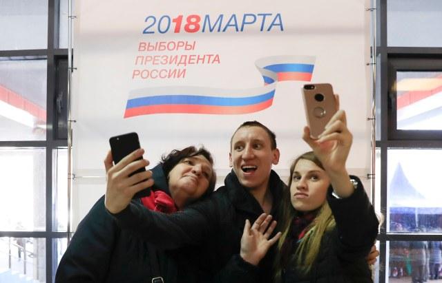 La gente toma fotos de autofoto mientras visitan una mesa de votación durante las elecciones presidenciales en Moscú, Rusia, el 18 de marzo de 2018. REUTERS / Tatyana Makeyeva