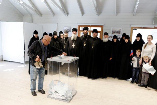 Los clérigos y monjas rusos posan para una foto grupal mientras un ciudadano ruso presenta su voto para las elecciones presidenciales de Rusia en una mesa electoral en Jerusalén, el 18 de marzo de 2018. REUTERS / Ronen Zvulun