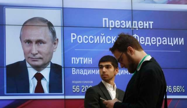 Hombres frente a una pantalla que muestra los resultados preliminares del presidente ruso, Vladimir Putin, en las elecciones presidenciales, en la sede de la Comisión Electoral Central de Rusia en Moscú, Rusia, el 19 de marzo de 2018. REUTERS / Sergei Karpukhin