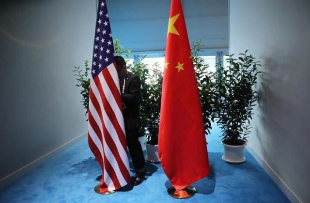 En la imagen de archivo un funcionario chino prepara las banderas de China y Estados unidos previo a la reunión bilatereal  en la cumbre de líderes del G20 en Hamburgo, Alemania.  8 de julio de 2017. REUTERS/Carlos Barria.