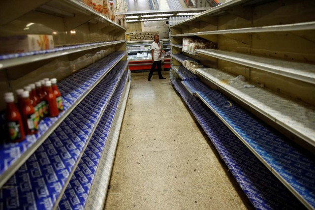 A woman looks at the almost empty shelves while she looks for groceries and goods in a supermarket in Caracas, Venezuela March 23, 2018. REUTERS/Carlos Garcia Rawlins