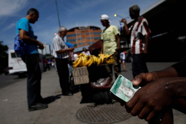A street vendor holds a stack of bolivar notes as people buy groceries in Caracas, Venezuela March 23, 2018. REUTERS/Carlos Garcia Rawlins