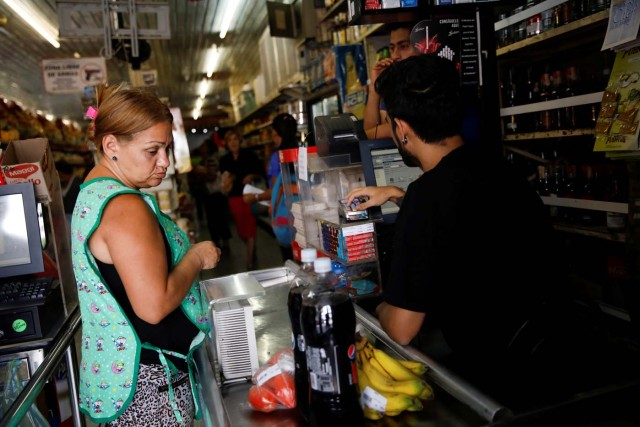 A woman pays for goods to the cashier at a supermarket in Caracas, Venezuela March 23, 2018. REUTERS/Carlos Garcia Rawlins